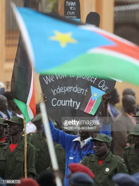 A man carries a sign as he joins a military parade during a ceremony in the capital Juba on July 09 2011 to celebrate South Sudan's independence from...