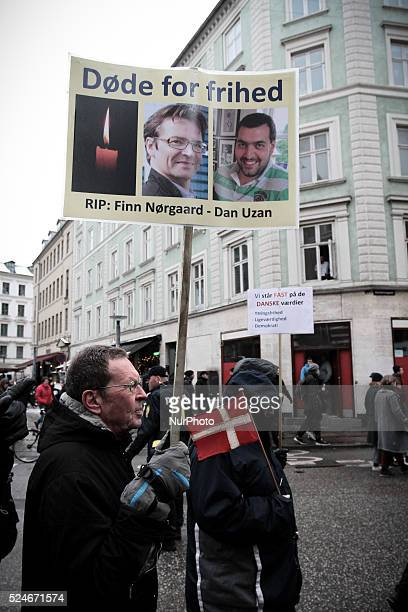 A man carries a sign depicting Finn N��rgaard and Dan Uzan the film director and security guard respectively who were murdered in an Islamic...