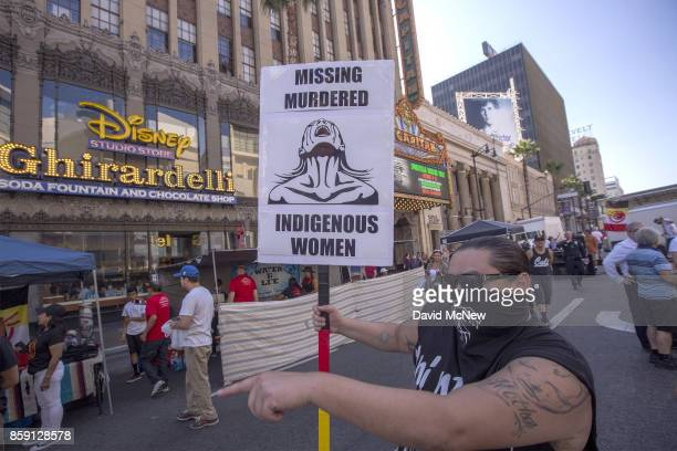 A man carries a sign on Hollywood Boulevard near the El Capitan Theatre and Jimmy Kimmel Live Studio during an event celebrating Indigenous Peoples...