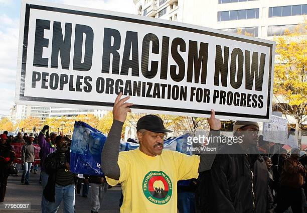 A man carries a sign that reads 'Ends Racism Now' while participating in a march around the Department of Justice to protest hate crime issues...
