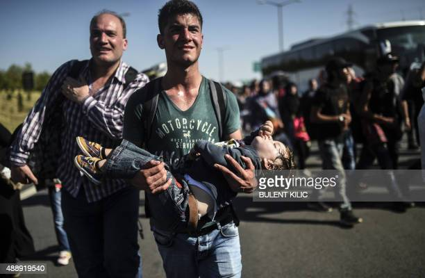 A man carries a sleeping child as Syrian migrants and refugees march along the highway towards the TurkishGreek border at Edirne on September 18 2015...