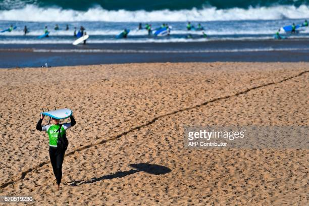 A man carries a surfboard after a surf lesson at Foz do Lizandro beach in Ericeira on November 5 2017 during a 2017 Web Summit surf event for...