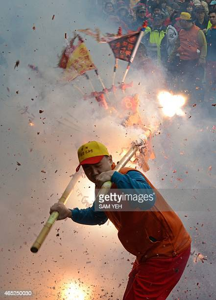 A man carries a Taoist god statue as fire crackers are detonated during a lunar festival event at the Yehliu harbor in New Taipei City on February 5...