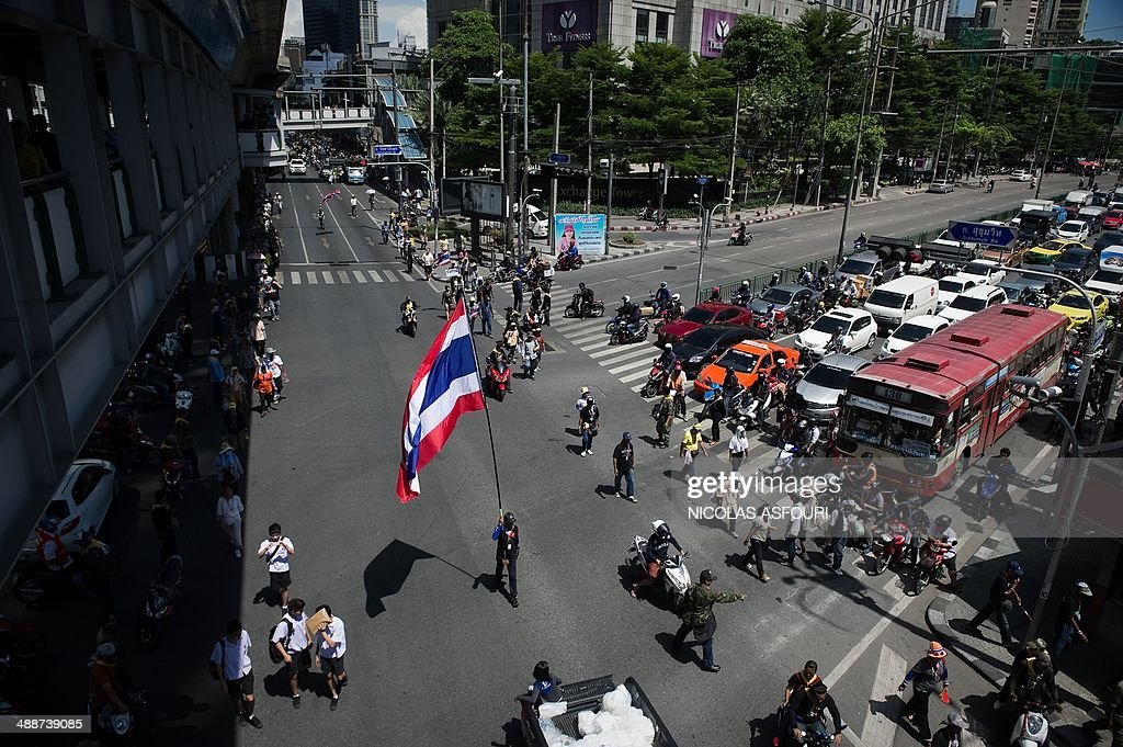 A man (C) carries a Thai flag as anti-government protesters march along a street in Bangkok on May 8, 2014. Thai protesters who have massed on Bangkok's streets for six months said on May 8 they would appoint a new government, following the removal of Premier Yingluck Shinawatra by a court. AFP PHOTO / Nicolas ASFOURI