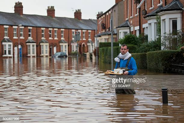 A man carries a tray of hot drinks and sausage sandwiches through flood water to residents remaining in their flooded properties in Carlisle northern...
