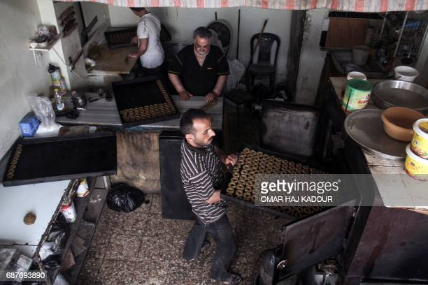 A man carries a tray of traditional pastries into an oven others prepare them from dough at a bakery in the rebelheld town of Binnish on the...