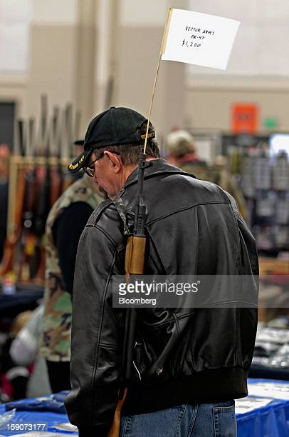 A man carries a Vector Arms AK47 for sale for $1200 at the Rocky Mountain Gun Show in Sandy Utah US on Saturday Jan 5 2013 A working group led by...