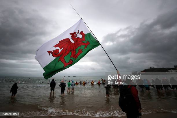 A man carries a Welsh flag at the swim leg of IRONMAN Wales on September 10 2017 in Tenby Wales