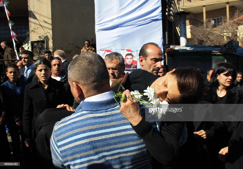 A man carries a woman, holding flowers during the funeral procession of Lebanese army captain Pierre Bashalana, in the city of Mraijat, on the outskirts of Beirut, on February 3, 2013. Bashalana was killed alongside sergeant Ibrahim Zahrman while several others were wounded in the clash with an unspecified number of unidentified gunmen in Arsal, a village near the border with Syria, who also sustained casualties on February 1. AFP PHOTO / STR