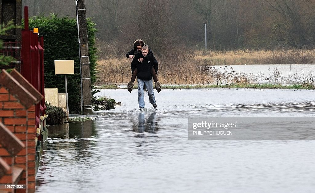 A man carries a woman on his back as he walks in a flooded street after the overflowing of the Lys river caused by recent heavy rainfalls, in Merville, northern France. AFP PHOTO / PHILIPPE HUGUEN