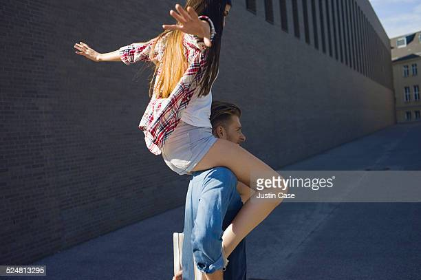 man carries a woman on his shoulders in the street