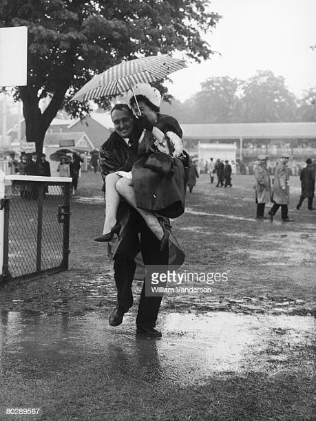 A man carries a woman over a muddy puddle as rain washes out the third day of racing at the Royal Ascot race meeting 18th June 1964