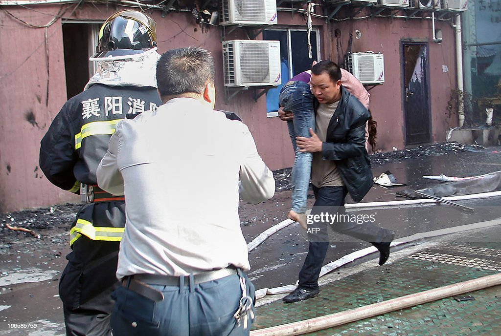 A man carries a woman survivor from a hotel that caught fire in Xiangyang, central China's Hubei province on April 14, 2013. The fire, started from an Internet cafe downstairs, resulted in 11 deaths and 50 injuries, local government reports annouced. CHINA