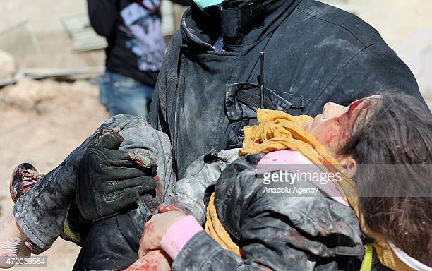 A man carries a wounded girl into an ambulance following a barrel bomb attack of Syrian regime forces on an oppositioncontrolled preschool in...