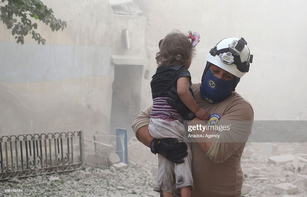 A man carries a wounded kid after Assad forces' airstrike, hit residential areas in Tal Zarazir Neighborhoof of Sukkeri District of Aleppo, Syria on May 31, 2016.