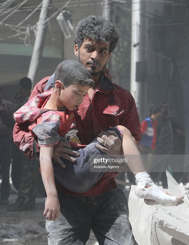 A man carries a wounded toddler after Assad forces hit residential areas with 'naval mines', thrown from helicopters in Kallese District of Aleppo, Syria on May 30, 2016.