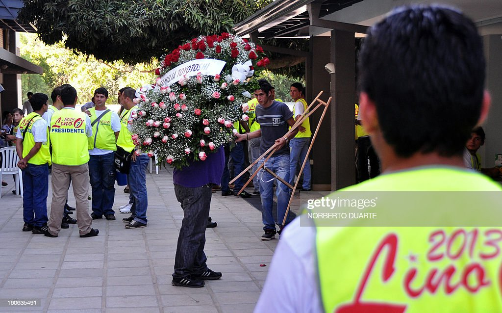 A man carries a wreath in honour of former Paraguayan general and UNACE party presidential candidate Lino Oviedo --who died along with his bodyguard Denis Galeano and pilot Ramon Picco Delmas in a helicopter crash on February 2-- at the party's headquarters in Asuncion on February 4, 2013. Oviedo, 69, the controversial presidential candidate who helped topple Paraguayan dictator Alfredo Stroessner in 1989, died when the aircraft crashed en route to Asuncion while returning from a campaign rally in northern Paraguay, prompting claims of foul play. AFP PHOTO/Norberto DUARTE