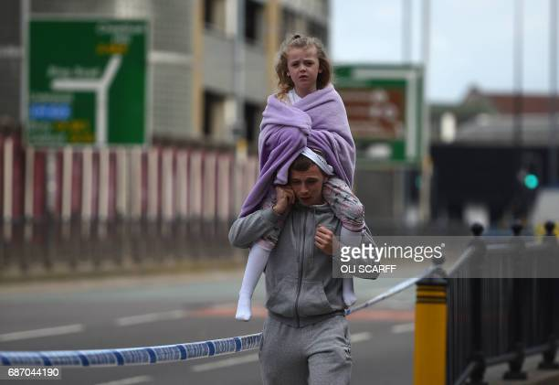 TOPSHOT A man carries a young girl on his shoulders near Victoria station in Manchester northwest England on May 23 2017 Twenty two people have been...