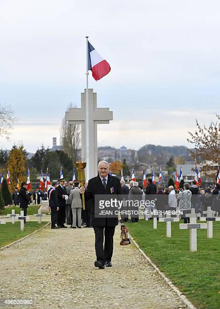 A man carries an eternal flame and torch during a dedication ceremony for seven unknown French WWI soldiers on November 10 2015 in Verdun eastern...