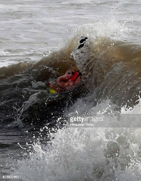 A man carries an idol of Hindu God Ganesha for immersion in the Versova sea on the fifth day at Versova in Mumbai on MondayHt