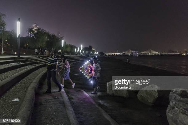 A man carries an illuminated kite featuring cartoon character SpongeBob SquarePants on the banks of the Yangtze River at night in Wuhan China on...