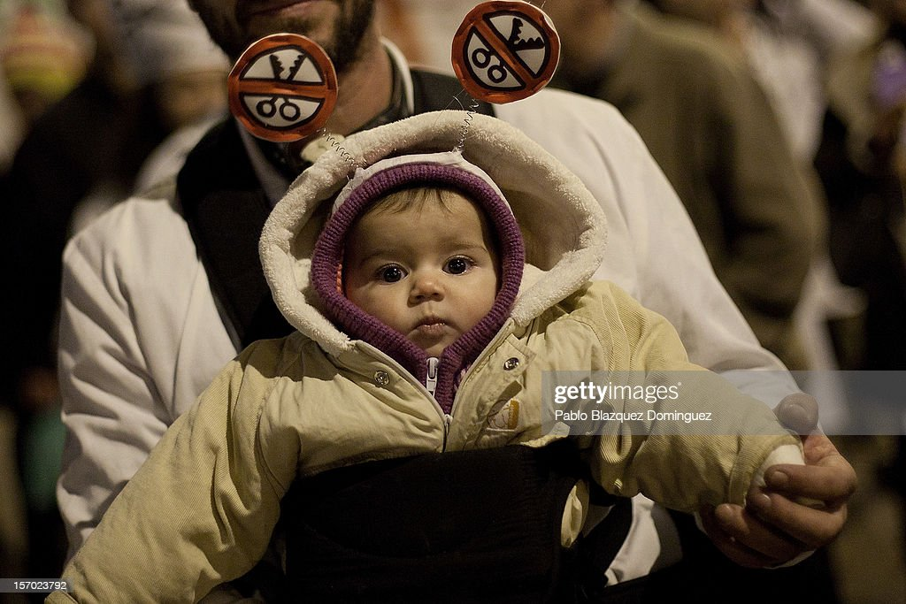 A man carries an infant wearing antennae amid other health workers during a demonstration held on the second day of a two-day general strike on November 27, 2012 in Madrid, Spain. For the first time all trade unions called for a 48-hour general health workers strike in the Madrid region after the regional government announced severe cuts and privatization of medical centers.