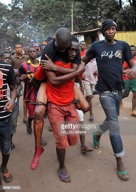 A man carries an injured demonstrator after opposition protesters clashed with police during a demonstration in Conakry on April 13 2015 Several...