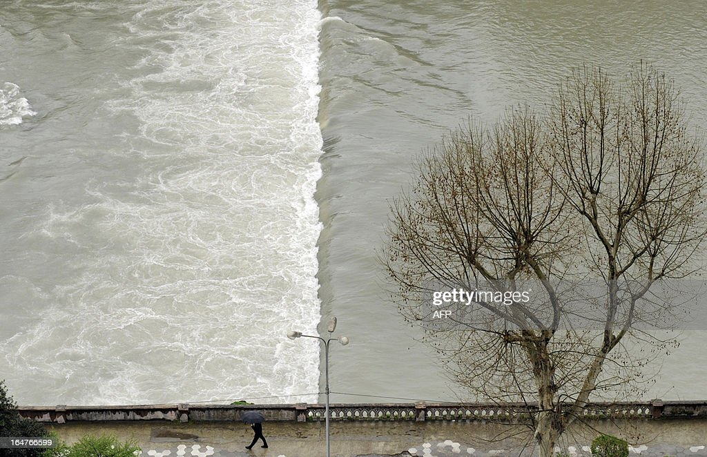 A man carries an umbrella as he walks along embankment of the Sochi River in the Russian Black Sea resort of Sochi, on March 27, 2013.