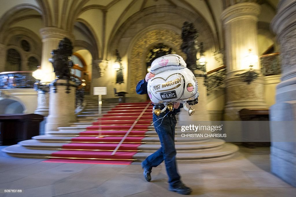 A man carries away a helium-filled wedding balloon after removing it from the foyer's ceiling of the city hall in Hamburg, northern Germany, on February 12, 2016. Preparations are under way for the so-called Matthiae-Mahl, a convention of representatives from political, social, economic and aristocratic life, that is attended in 2016 by the German Chancellor Angela Merkel and British Prime Minister David Cameron. / AFP / dpa / Christian Charisius / Germany OUT