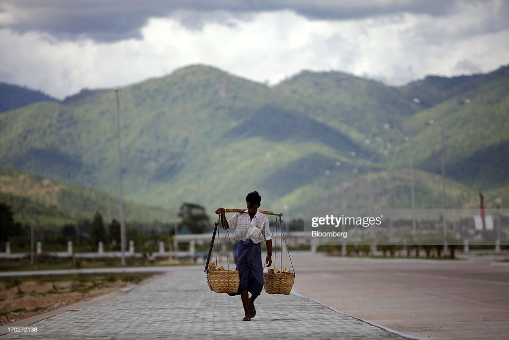 A man carries baskets filled with logs of wood past a construction site in Naypyidaw, Myanmar, on Friday, June 7, 2013. President Thein Sein has allowed more political freedom and loosened economic controls since coming to power two years ago, prompting the U.S. and other nations to ease sanctions. Photographer: Dario Pignatelli/Bloomberg via Getty Images