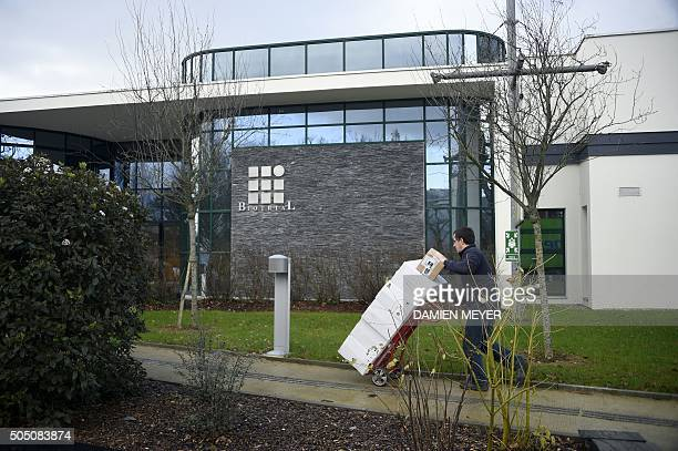 A man carries boxes on January 15 2016 in front of the Biotrial laboratory building in Rennes where a clinical trial of an oral medication left one...