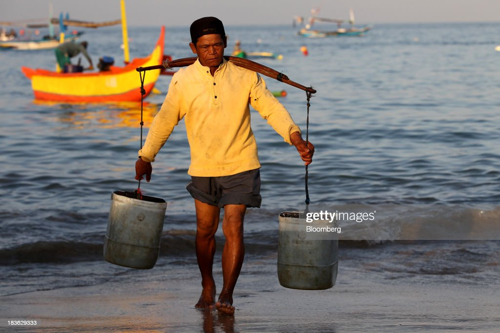 A man carries buckets of water at Kedonganan beach in Jimbaran, Bali, Indonesia, on Saturday, Oct. 5, 2013. Indonesia's central bank kept its key interest rate unchanged after its most aggressive tightening cycle in almost eight years as inflation pressure eased. Photographer: SeongJoon Cho/Bloomberg via Getty Images