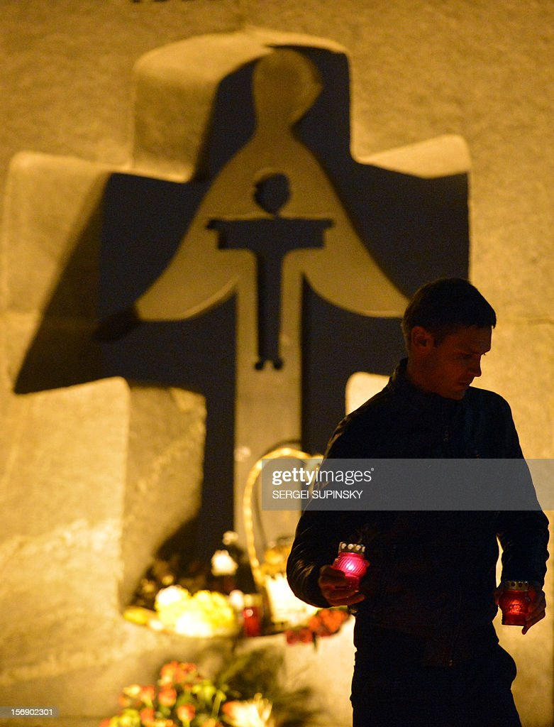A man carries candles in memory of the victims of the Holodomor famine in Kiev on November 24, 2012. Ukraine marked 80 years since the Stalin-era Holodomor famine, one of the darkest pages in its entire history that left millions dead and which is regarded by many as a genocide. The 1932-33 famine took place as harvests dwindled and Josef Stalin's Soviet police enforced the brutal policy of collectivising agriculture by requisitioning grain and other foodstuffs. AFP PHOTO/ SERGEI SUPINSKY