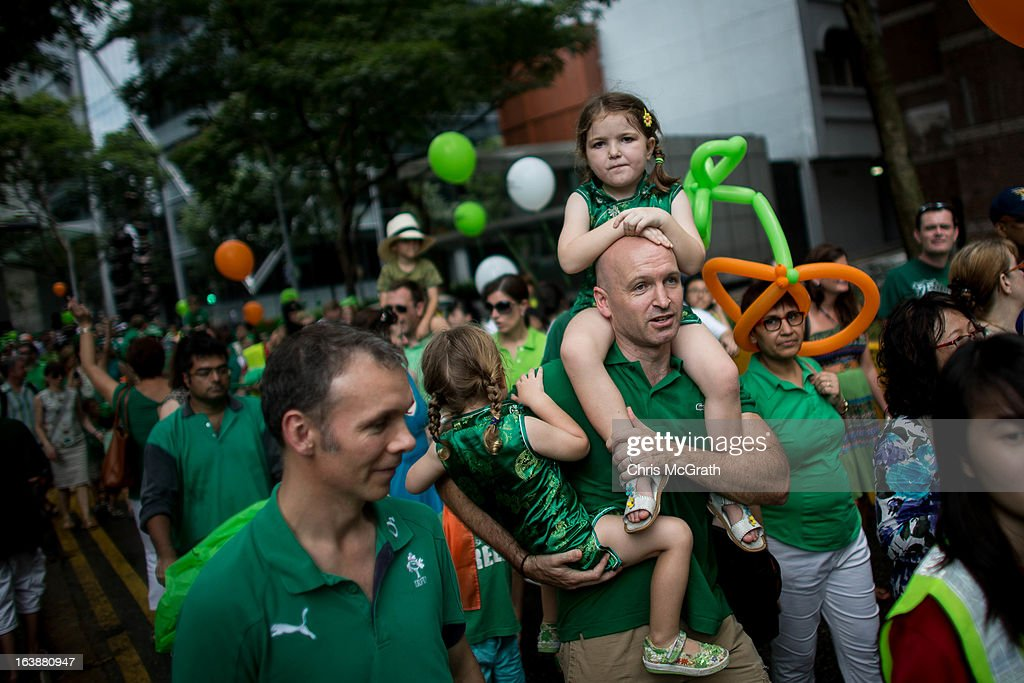 A man carries children down the street during the St Patricks Day Parade at Boat Quay on March 17, 2013 in Singapore. Singapore's Irish community gathered at Boat Quay for a three-day-long St Patrick's Day Street Festival which featured street performances, buskers, and Irish food and drink.