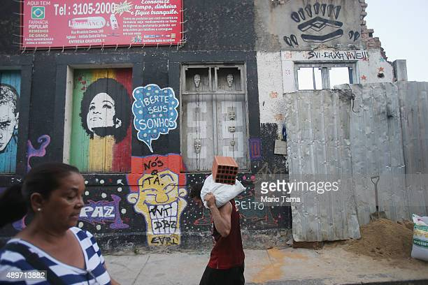 A man carries construction materials in the Providencia community or 'favela' on September 23 2015 in Rio de Janeiro Brazil The historic 'favela' is...