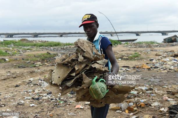 A man carries debris from demolished makeshift homes following eviction notices served on residents of IlajeBariga waterfront settlement mostly...