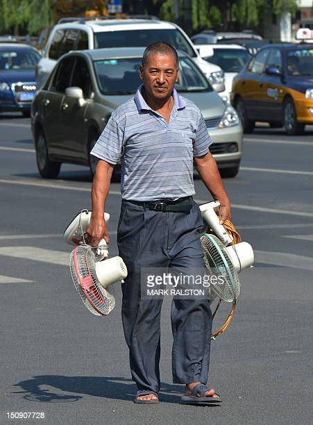 A man carries fans along a busy street as high summer temperatures returned in Beijing on August 29 2012 Summer in Beijing which runs from early June...