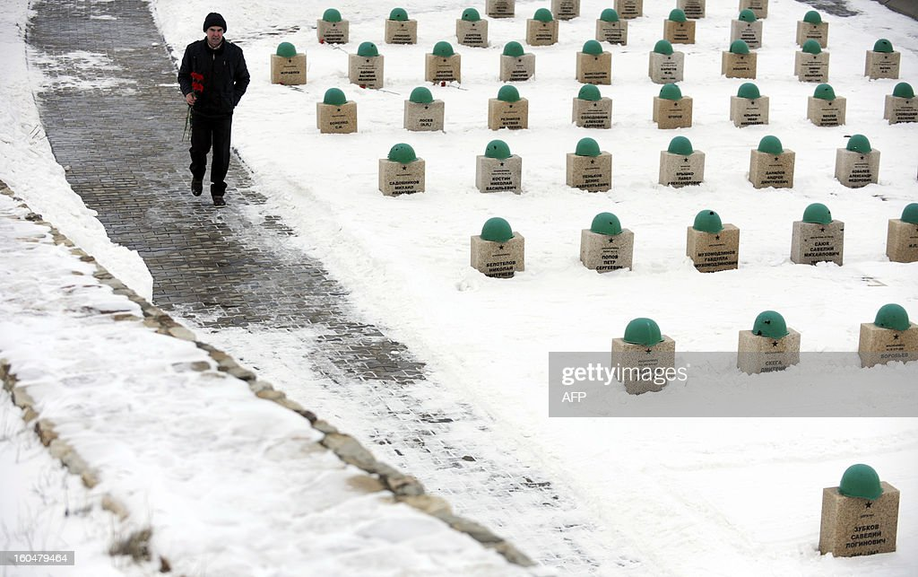 A man carries flowers as he walks past gravestones of the Red Army soldiers who died in the Battle of Stalingrad during the World War II, at a military cemetery in the Russian village of Rossoshka, some 40 km outside the city of Volgograd, formerly Stalingrad, on February 1, 2013. In a new display of national pride and reminder of its status as a world power, Russia remembers this weekend the Red Army victory in the battle of Stalingrad over invading Nazi forces, one of the bloodiest battles in human history.