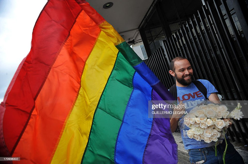 A man carries flowers at the entrance of the courthouse in Bogota, Colombia, on June 20, 2013, as gay couples fill documents to apply for registration of their marriage. From today Colombia will enter into a legal puzzle on gay marriage, as gay couples will go to notaries and judged without knowing if they will come out with the document as desired, given the legal vacuum that persists for such unions. AFP PHOTO/Guillermo LEGARIA