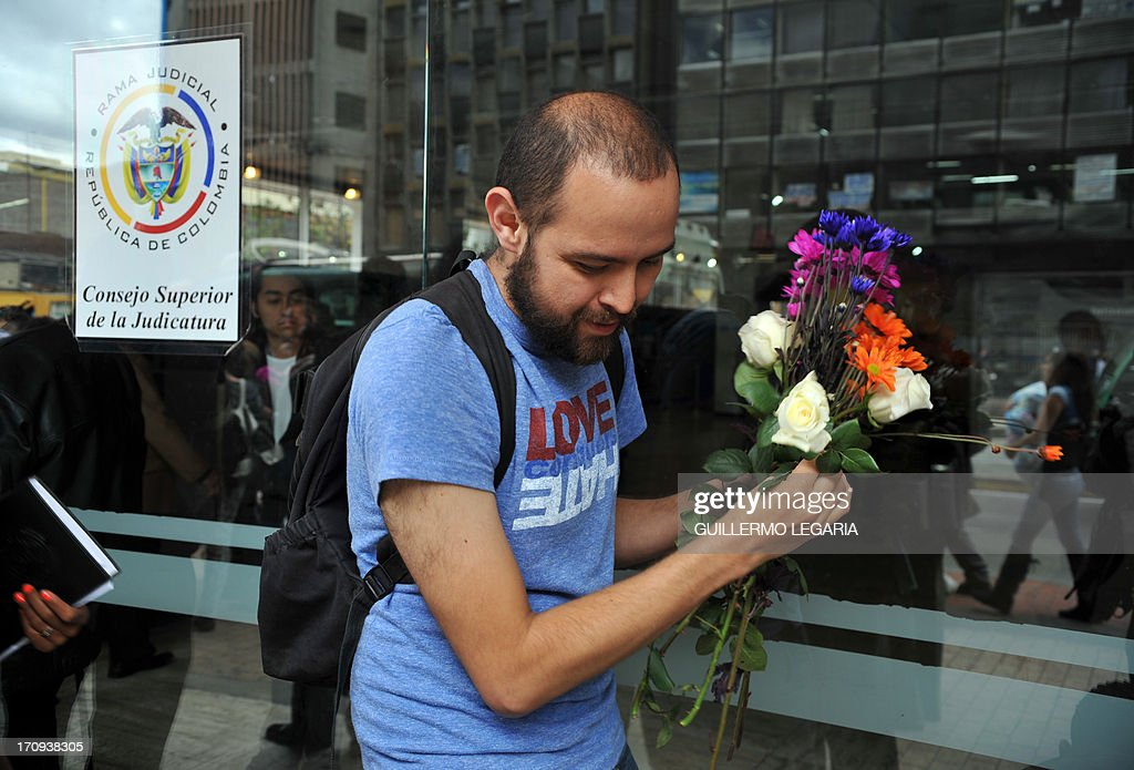 A man carries flowers at the entrance of the courthouse in Bogota, Colombia, on June 20, 2013, as gay couples fill documents to apply for the registration of their marriage. From today Colombia will enter into a legal puzzle on gay marriage, as gay couples will go to notaries and judged without knowing if they will come out with the document as desired, given the legal vacuum that persists for such unions. AFP PHOTO/Guillermo LEGARIA