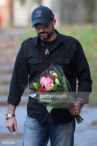 A man carries flowers to lay outside the Oxfordshire home of British pop singer George Michael on December 26 2016 in Goring England Singer George...