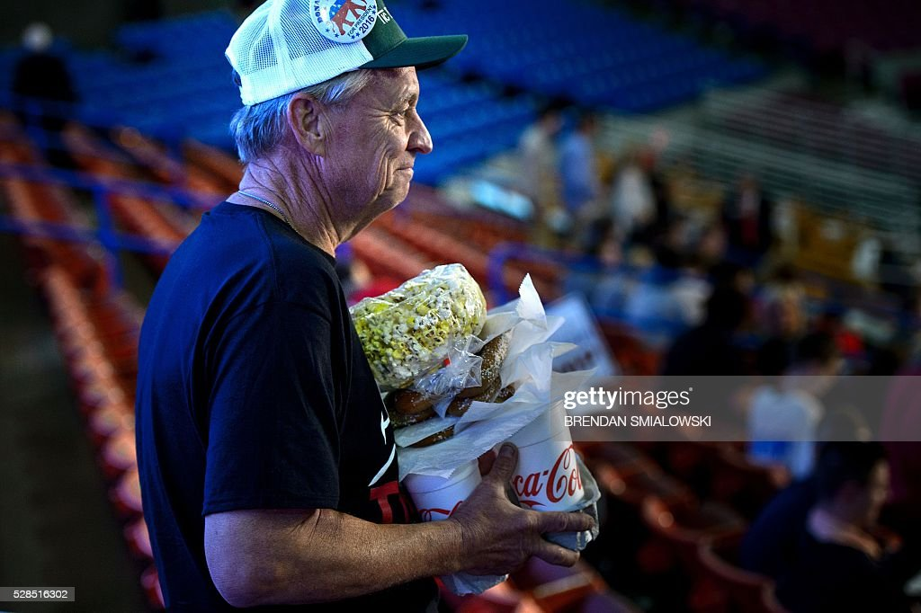 A man carries food to his seat before a rally for US Republican presidential candidate Donald Trump May 5, 2016 in Charleston, West Virginia. / AFP / Brendan Smialowski