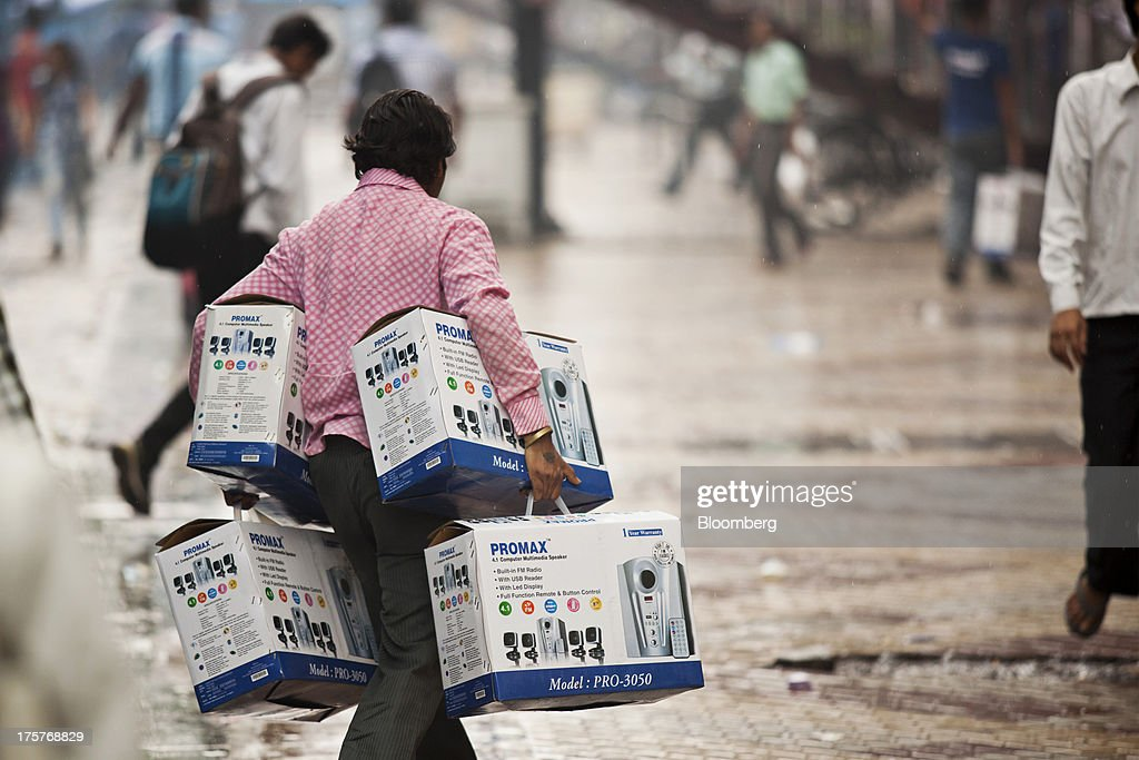 A man carries four boxed sets of Promax computer speakers in Nehru Place IT Market, a hub for the sale of electronic goods and computer accessories, in downtown New Delhi, India, on Wednesday, Aug. 7, 2013. India's consumer price index (CPI) figures for July are scheduled to be released on August 12. Photographer: Graham Crouch/Bloomberg via Getty Images