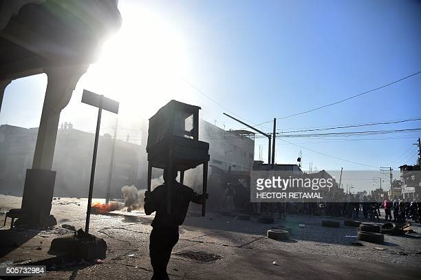 A man carries furniture as he walks past a burning tires placed by demonstrators during clashes in a protest in PortauPrince on January 19 2016...