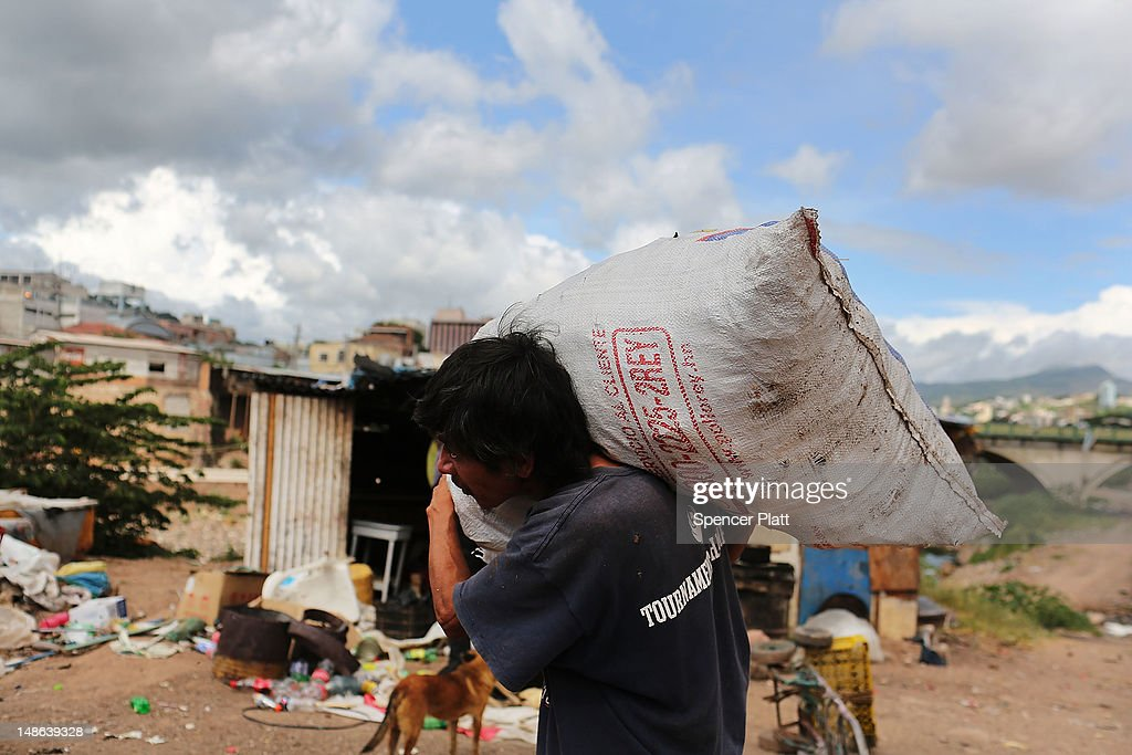 A man carries garbage to a dumpster where in a gang infested neighborhood on July 17 2012 in Tegucigalpa Honduras Honduras now has the highest per...