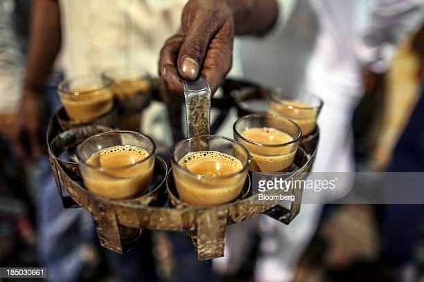 A man carries glasses of Indian spiced chai tea in Bangalore India on Friday Oct 11 2013 Reserve Bank of India Governor Raghuram Rajan has turned the...
