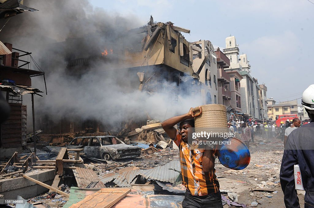 A man carries good salvaged from building stocked with fireworks on fire in Lagos on December 26, 2012. Fire ripped through a crowded neighbourhood in Nigeria's largest city and wounded at least 30 people after a huge explosion rocked a building believed to be storing fireworks, officials said.