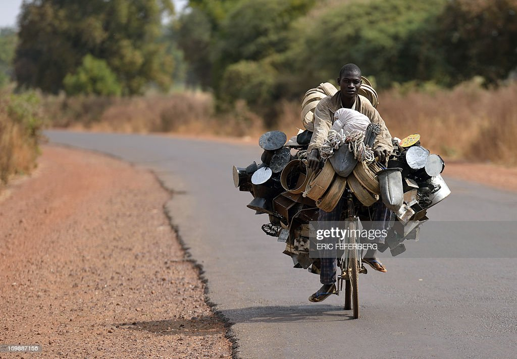 A man carries good to sell as he rides a bicyle en route for the market on January 22, 2013 near Segou, 240km North of Bamako. Mali's army chief today said his French-backed forces could reclaim the northern towns of Gao and fabled Timbuktu from Islamists in a month, as the United States began airlifting French troops to Mali.