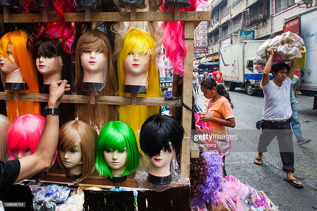 A man carries goods on his head as he walks past a stall selling wigs at the Divisoria market in Manila, the Philippines, on Tuesday, Jan. 22, 2013. Philippine government bonds advanced on speculation the central bank will hold its benchmark interest rate at a record low at a meeting tomorrow, supporting demand for the nation's debt. Photographer: Julian Abram Wainwright/Bloomberg via Getty Images