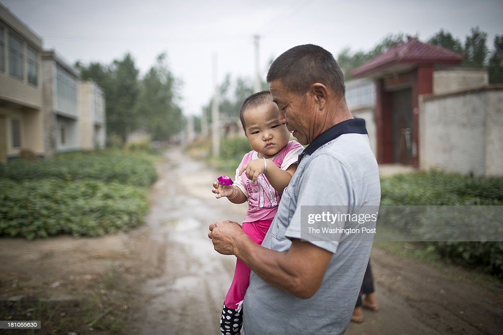 A man carries hhis grand daugther down a street at a rural village near Fuyang, Anhui Province, China on 28 August 2013. As able-bodied adults seek work in cities in hopes of better income, more and more villages in China are inhabited mostly by the elderly and children.
